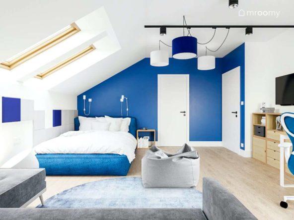 Miękkie duże tapicerowane niebieskie łóżko niebieska ściana i fotel sako w dużym poddaszowym pokoju nastolatka