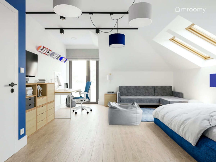 Biały jasny pokój nastolatka na poddaszu z sofą łóżkiem biurkiem i regałami ze sklejki z miejscem na deskorolki