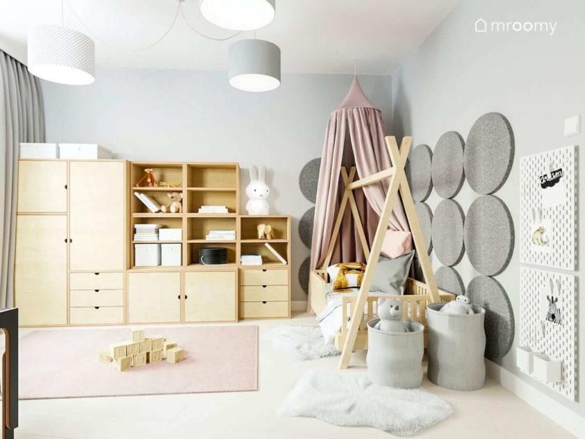 Łóżko tipi z baldachimem miękkie panele na ścianie modułowa szafa i regały ze sklejki i różowy dywan w pokoju małej dziewczynki