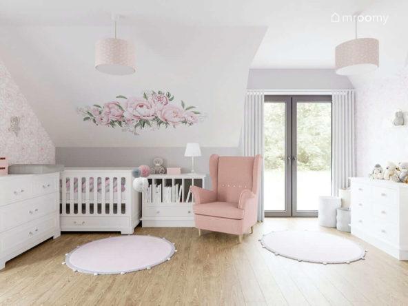 Jasny poddaszowy pokój dla dziewczynki niemowlaka z białymi meblami różowym fotelem i naklejką w kwiaty na ścianie