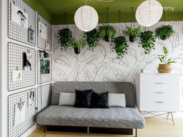 Rozkładana sofa organizery na ścianie tapeta w motywy kwiatów i kwiaty zwisające z sufitu w pokoju nastolatki