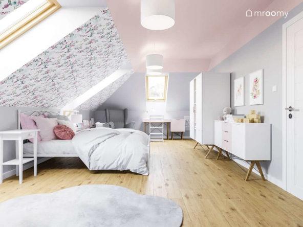 Pokój dziewczynki na poddaszu z dużym łóżkiem białymi meblami różowym sufitem szarymi ścianami i tapetą w kwiaty