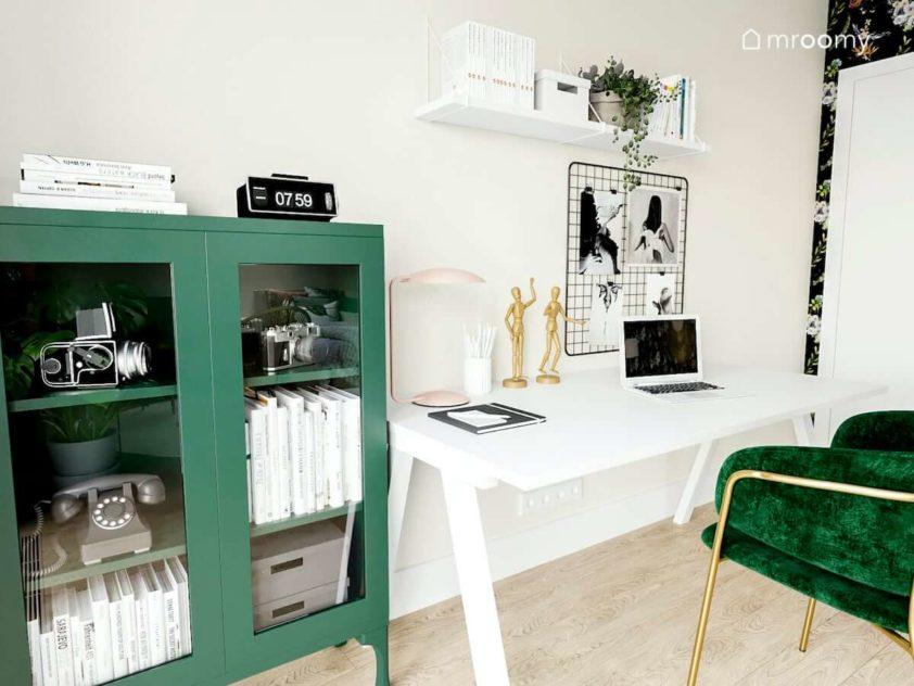 Miejsce do nauki w pokoju nastolatki z białym biurkiem nad którym są metalowe organizery i zielonym regałem z zamykanymi szklanymi drzwiami