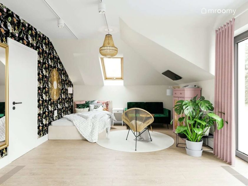 Duże łóżko zielona sofa i rattanowy fotel w pokoju nastolatki ze skosami