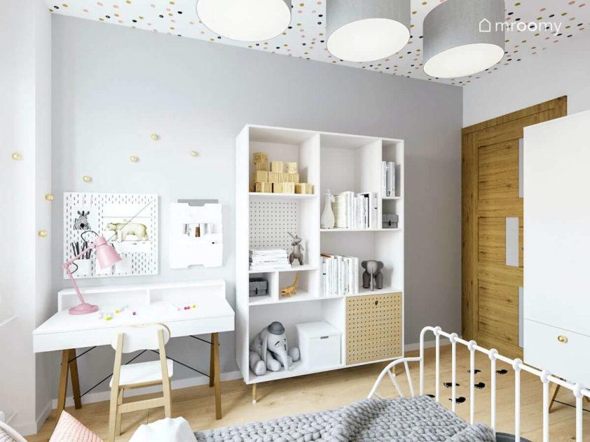 Stylowe białe biurko na drewnianych nogach z organizerami powieszonymi nad nim ładny biało-drewniany regał przy szarej ścianie w pokoju małej romantycznej dziewczynki