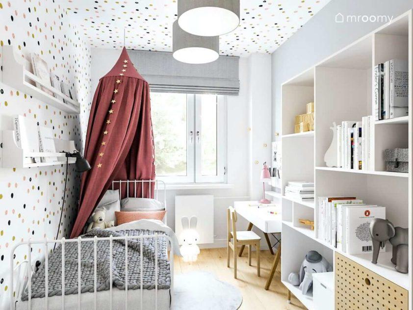 romantyczny pokój dla małej dziewczynki z mnóstwem zabawnych kropek na ścianie i suficie z metalowym łóżkiem z baldachimem białym regałem i biurkiem