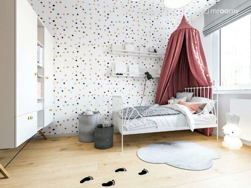 Metalowe białe łóżko z baldachimem dywan chmurka i ściana w kropki w pokoju małej dziewczynki