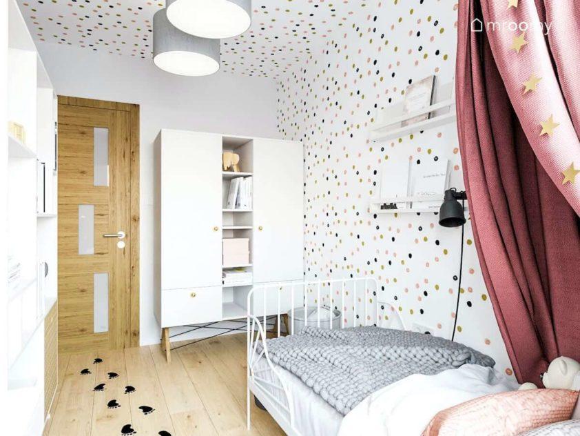 Biała szafa metalowe łózko z baldachimem tapeta w kropki i naklejki na podłodze ze śladami stópek w pokoju dla małej dziewczynki