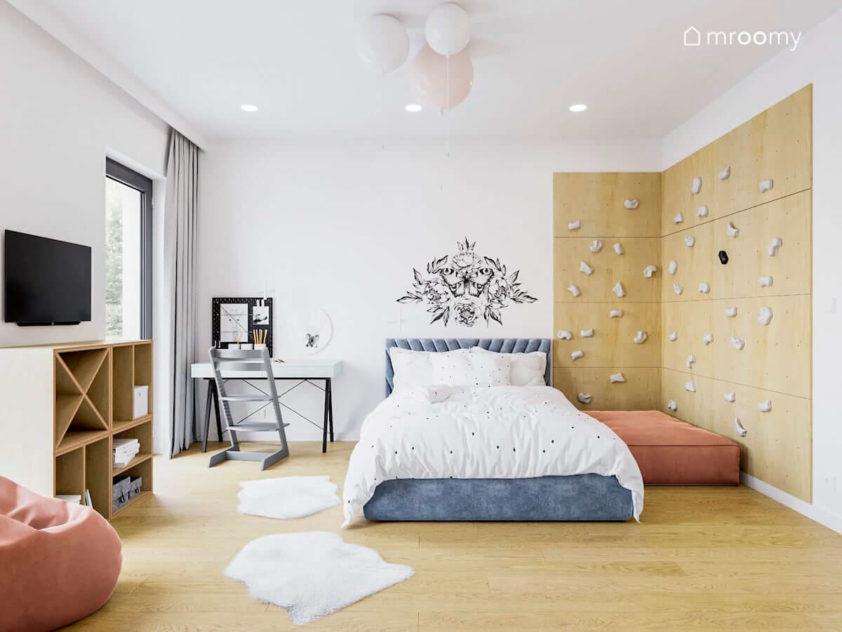 Ścianka wspinaczkowa obok tapicerowanego łóżka i białego biurka w pokoju dla dziewczynki