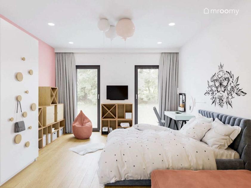 Pokój dla dziewczynki z dużym niebieskim łóżkiem meblami ze sklejki i różowymi ścianami