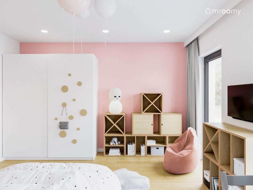 Różowa ściana z białą szafą obok worek sako i regały ze sklejki w pokoju dziewczynki