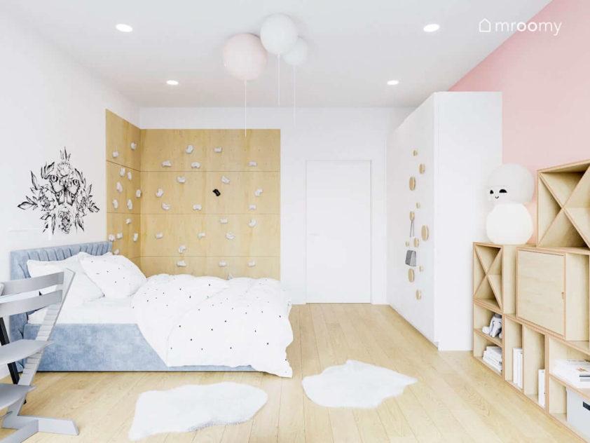Pokój małej dziewczynki ze ścianką wspinaczkową tapicerowanym łóżkiem i dużą białą szafą z dodanymi uchwytami ze sklejki