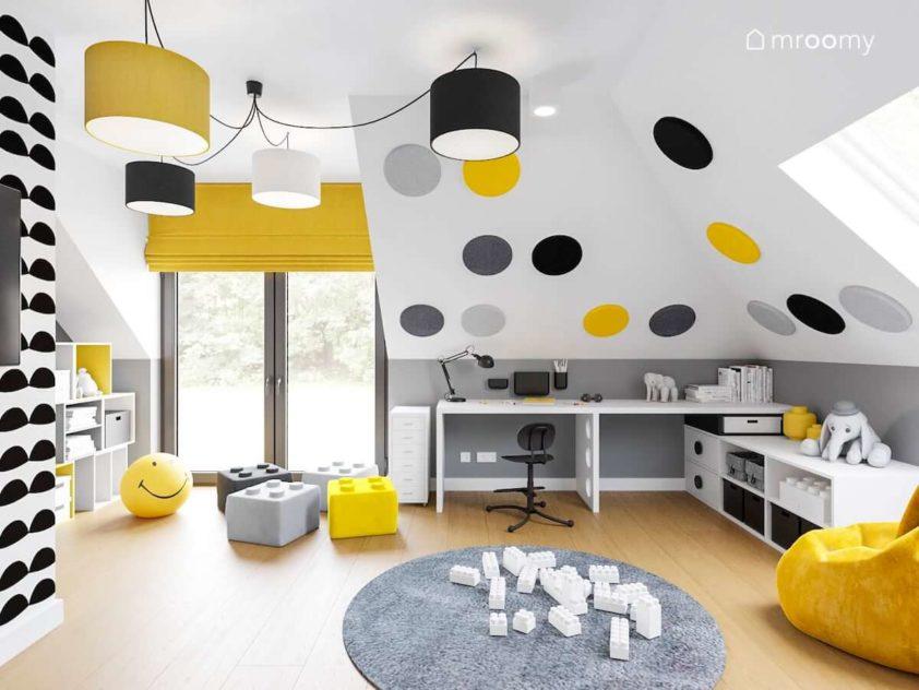 Miejsce do nauki z biurkiem obok duże okno z żółtą roletą rzymską i pufy w kształcie klocków lego w pokoju dziecka