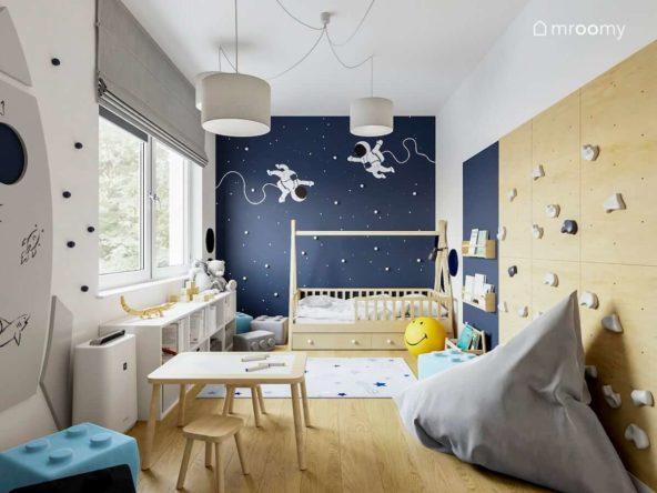 Niebieska ściana z gwiazdami i astronautami w pokoju chłopczyka z łóżkiem tipi stoliczkiem i ścianką wspinaczkową