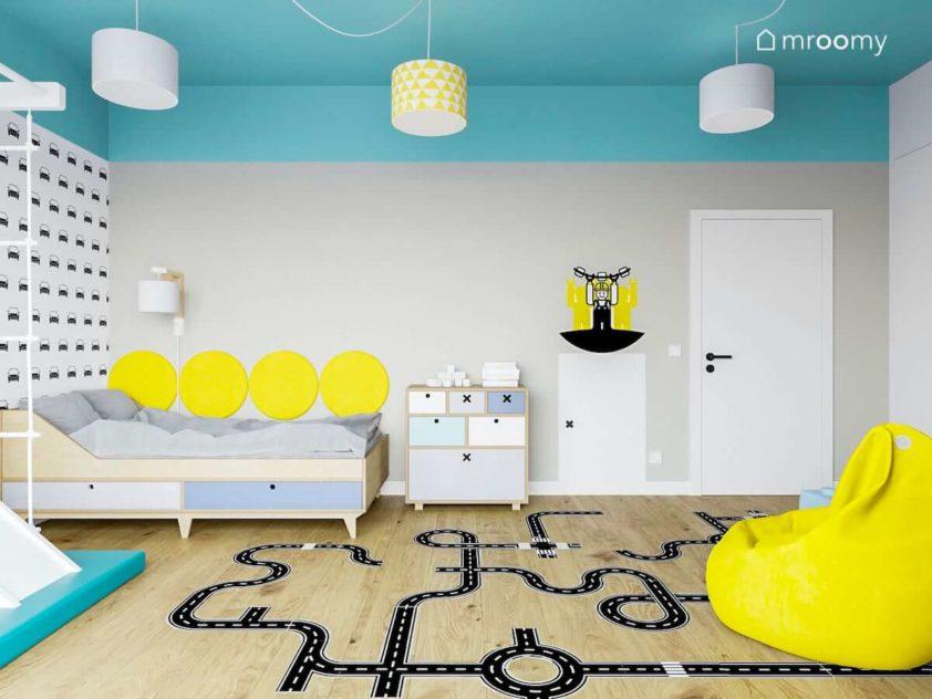 Radosny pokój dziecięcy chłopca z łóżkiem naklejkami podłogowymi żółtymi dodatkami i jasno turkusowym sufitem