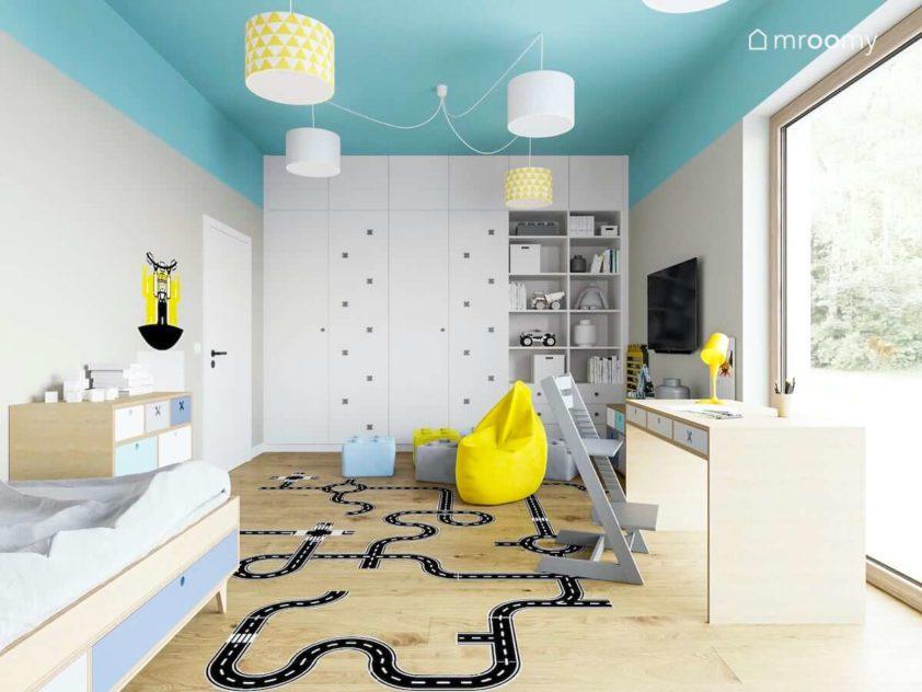 Pokój chłopca z kolorowym sufitem białą szafą naklejką podłogową biurkiem i szarym krzesłem