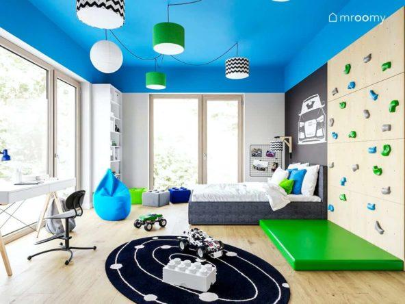 Pokój chłopca w niebieskie zielone czarne białe kolory ze ścianką wspinaczkową dużym łóżkiem i kolorowym sufitem