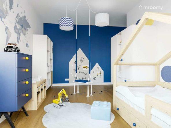 Łóżko domek białe meble i niebieska ściana z tablicą suchościeralną przy huśtawce w pokoju małego chłopca