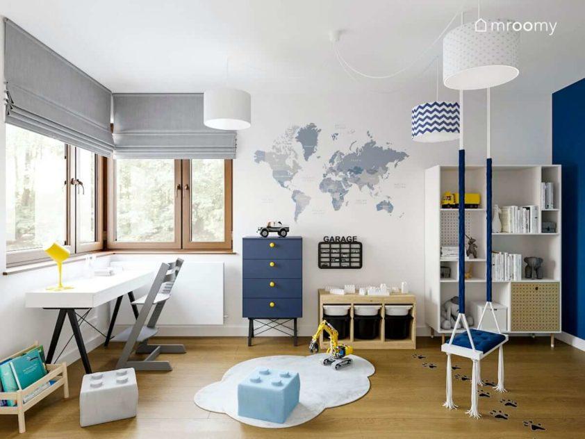 Granatowa komoda obok białego regału przy ścianie z tapetą z mapą świata narożne okno i huśtawka w pokoju dziecka małego chłopca