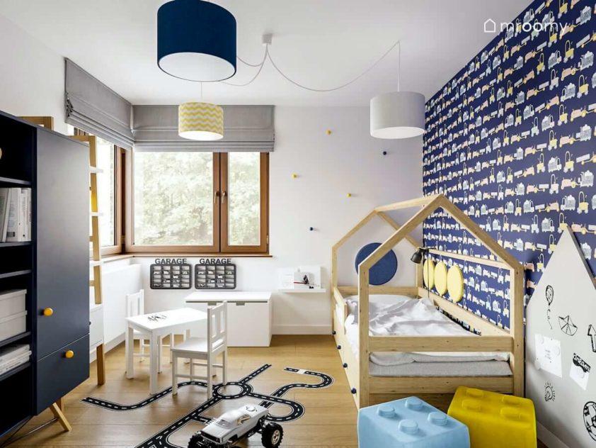 Granatowa tapeta w pojazdy łóżko domek biały stolik i naklejki podłogowe jezdnie w pokoju małego chłopca