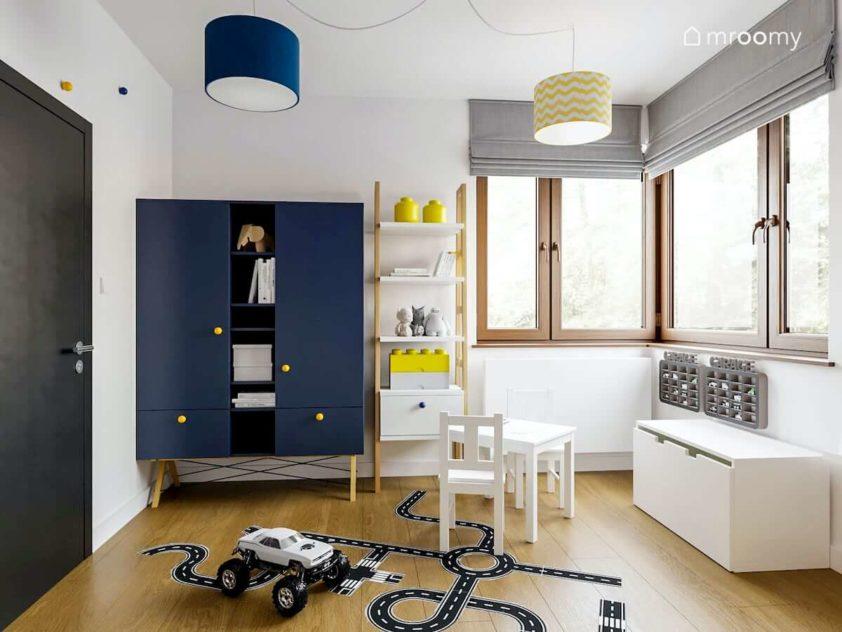 Granatowa komoda z żółtymi gałkami naklejki na podłogę w ulice biały regał i szare rolety rzymskie w pokoju przedszkolaka