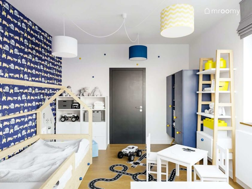 Pokój chłopca przedszkolaka w którym jest łóżko domek niebieskie i białe meble i żółte dodatki