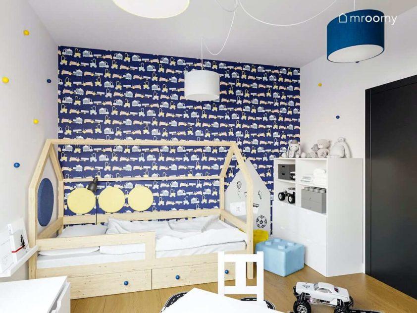 Ściana w granatową tapetę z autkami obok łóżko domek i biały regał w pokoju dziecka przedszkolaka