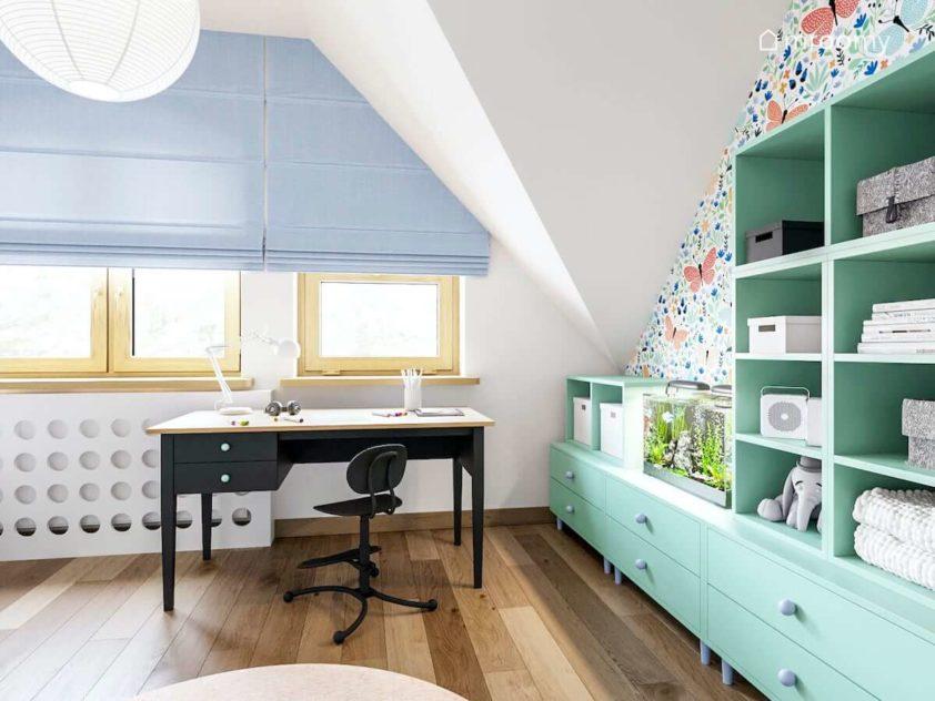 Biurko obok okna z niebieskimi roletami rzymskimi obok zielonych mebli i ściany z tapetą w motyle w pokoju dziewczynki