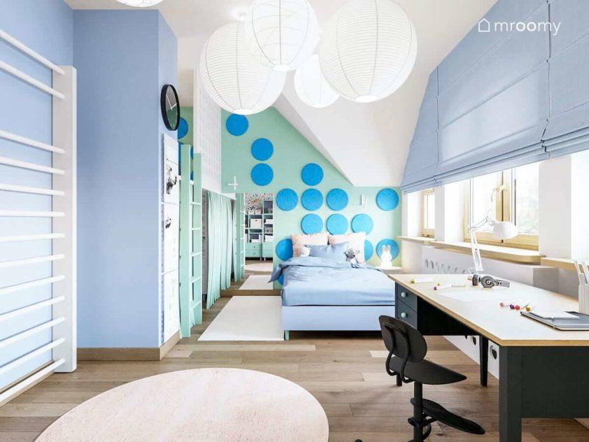 Pokój małej dziewczynki z antresolą niebieskim łóżkiem za którym jest ściana z okrągłymi miękkim panelami biurko i rolety rzymskie na oknie