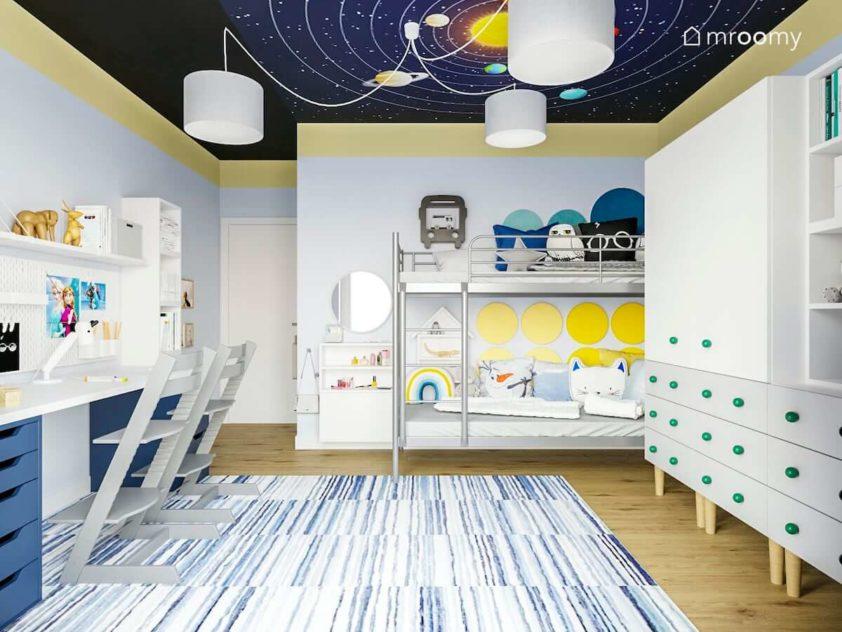 Łóżko piętrowe metalowe dywan w paski szafa z kolorowymi gałkami i sufit z planetami w pokoju chłopca i dziewczynki