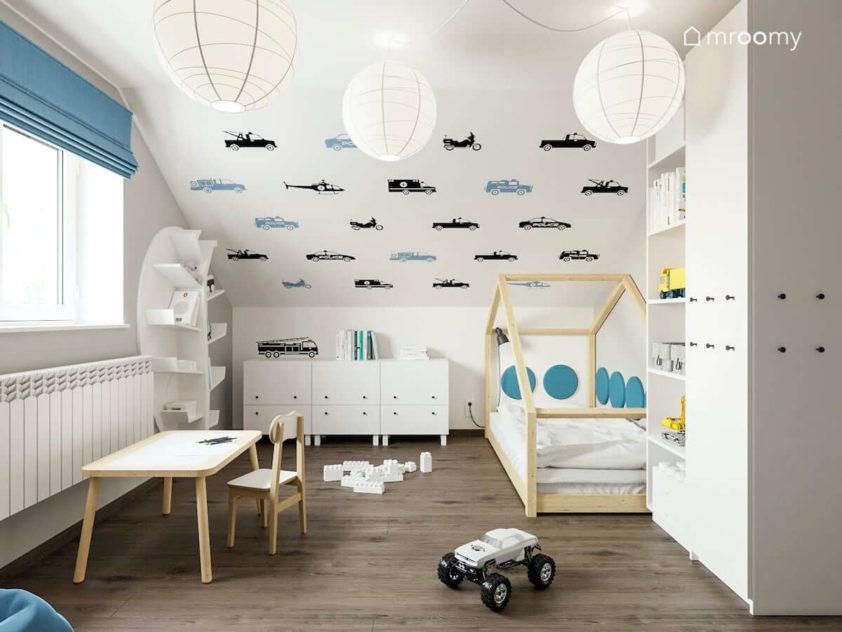 Łózko domek pod skosem z tapetą w samoloty biała szafa w pokoju przedszkolaka chłopca