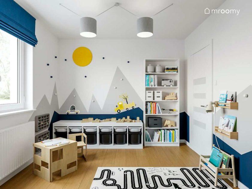 Pokój małego chłopca z motywem gór na ścianie i jasnymi meblami z szarym dywanem droga