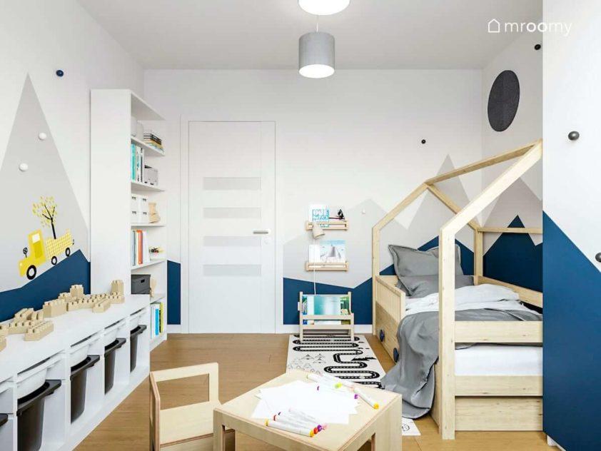 Drewniane łózko domek białe meble stoliczek z krzesełkiem i góry na ścianie w małym pokoju chłopca