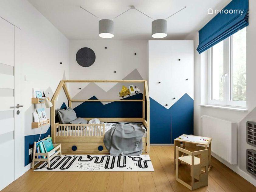 Szafa i ściana z motywem gór łóżko domek i półka na książki w pokoju przedszkolaka chłopca