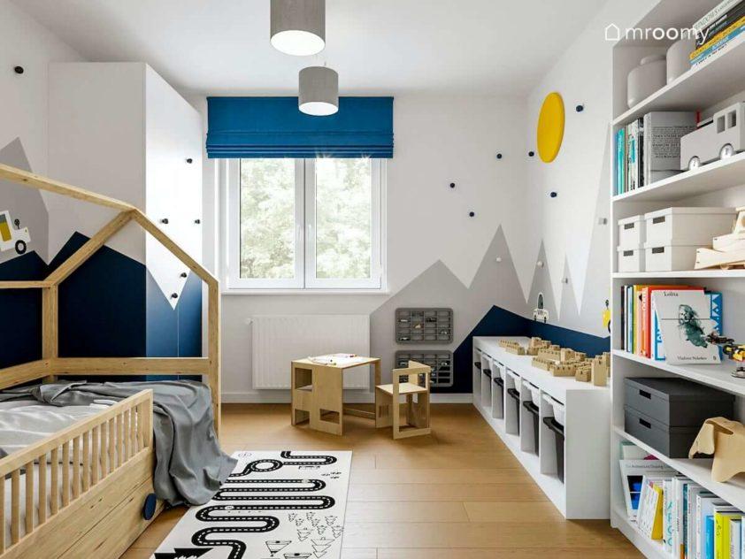 góry namalowane na ścianie biały regał stoliczek z krzesełkiem i granatowe dodatki w pokoju małego chłopca