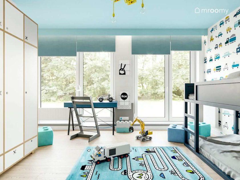 Pokój małego chłopca z dużym oknem balkonowym przy którym stoi niebieskie biurko i pufy lego na podłodze