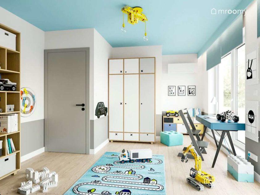 Biała szafa z motywami kółko i krzyżyk niebieskie biurko z regulowanym drewnianym krzesłem kolorowy sufit i dywan z drogą w pokoju przedszkolaka