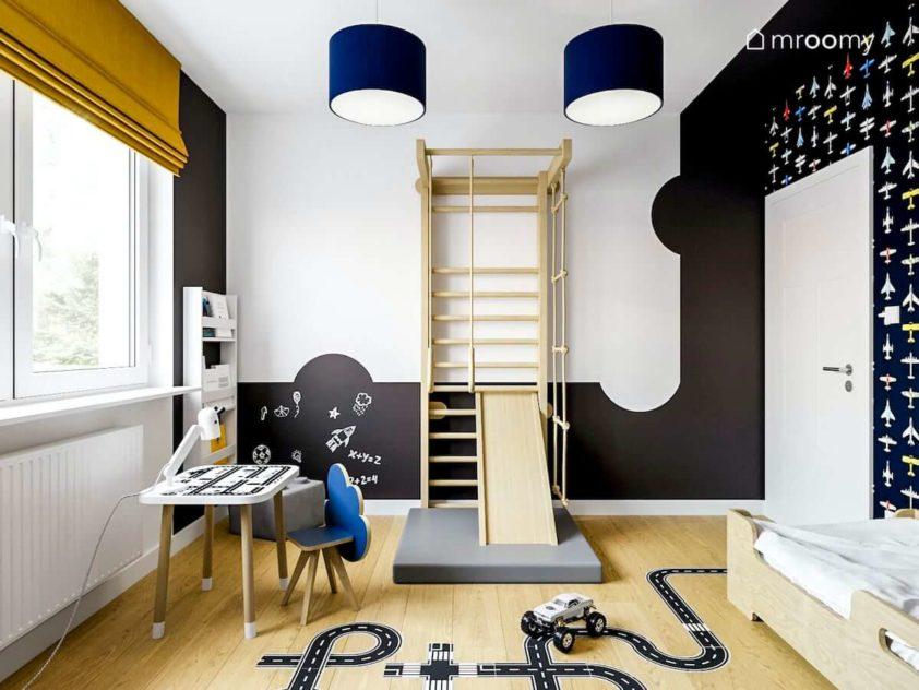 Drabinka stolik z krzesełkiem i czarna farba tablicowa w pokoju chłopca przedszkolaka z naklejkami na podłodze