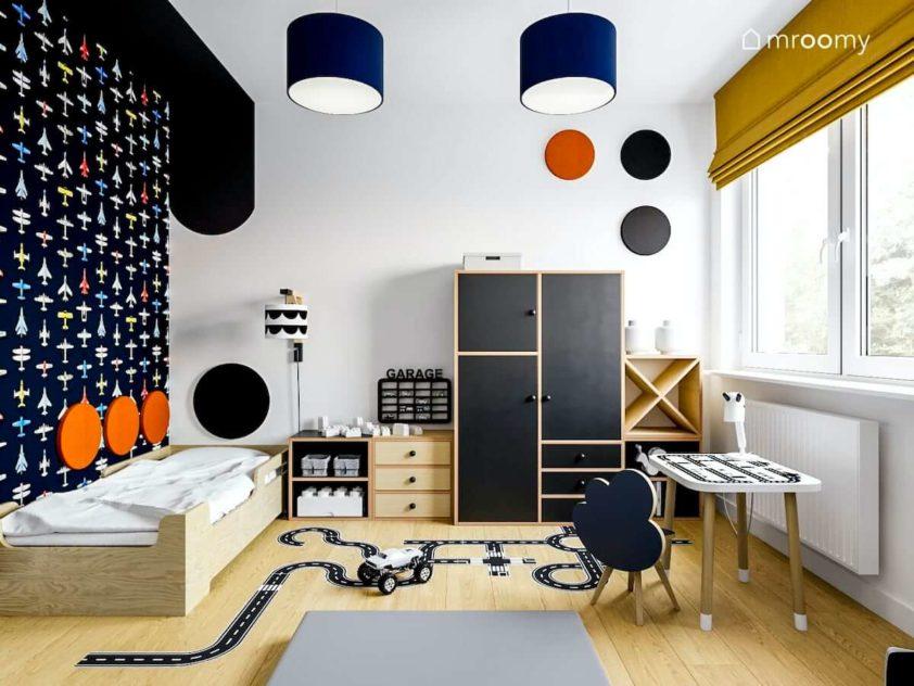 Meble ze sklejki w kolorze czarnym tapeta w samoloty i krzesełko ze stolikiem w pokoju małego chłopca