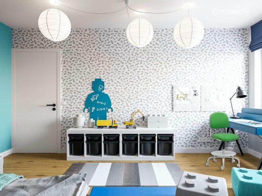 Ściana z tapetą z motywem lego białe abażury dywan w paski i zielone krzesło do biurka w pokoju szkolnego chłopca