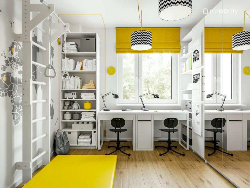 Biurka pod oknem drabinka gimnastyczna żółta roleta lampy we wzory w pokoju dla rodzeństwa dwójki chłopców