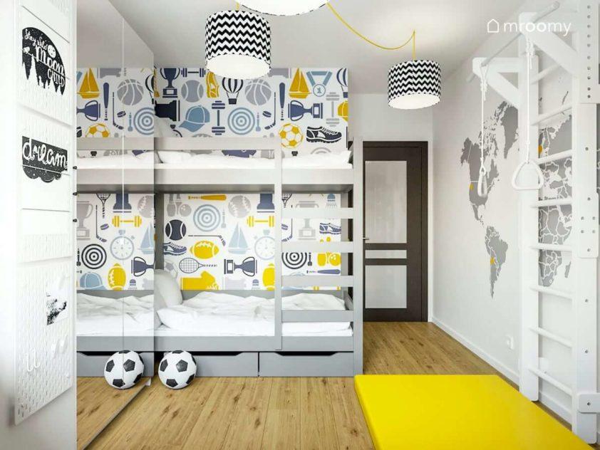 Ściany przy piętrowym łóżku pokryte tapetą w sportowy wzór w pokoju dwóch szkolnych chłopców