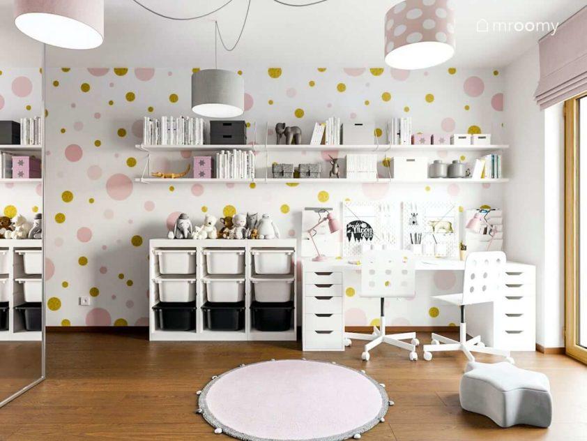 Duże biurko regały na książki w pokoju małych dziewczynek z tapetą w różowe kropki