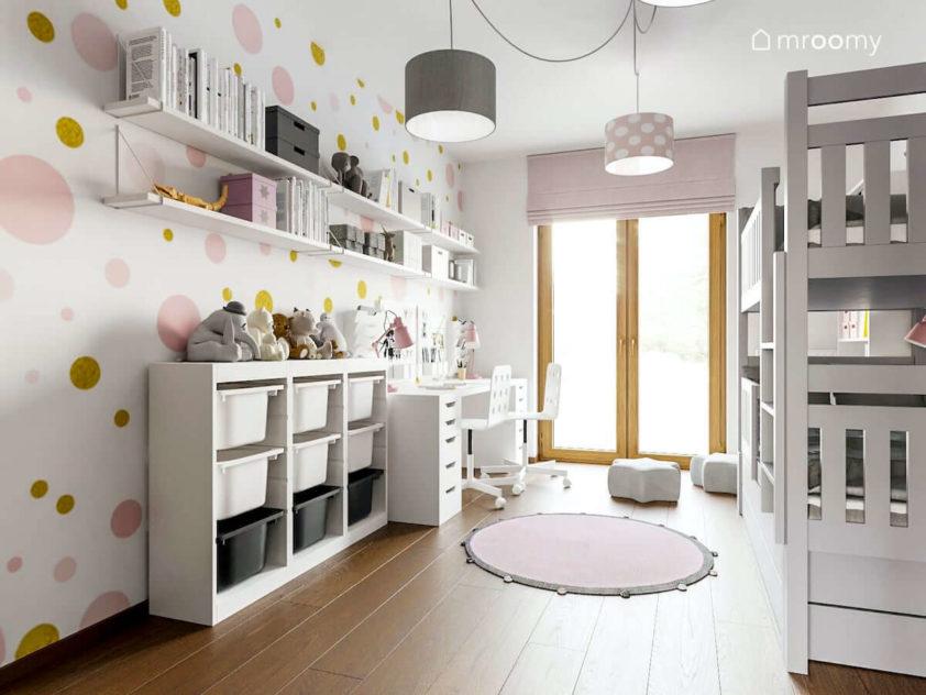Dwuosobowe białe biurko różowa roleta tapeta w złoto-różowe kropki i okrągły dywan w pokoju małych dziewczynek