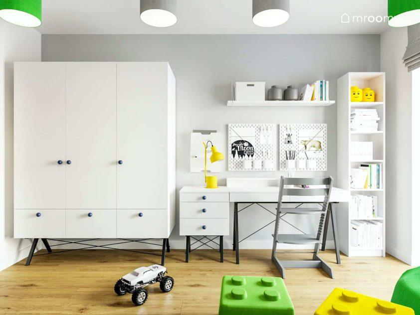 Białe biurko i szafa na tle szarej ściany z białymi organizerami nad biurkiem i szarym krzesłem w pokoju chłopca