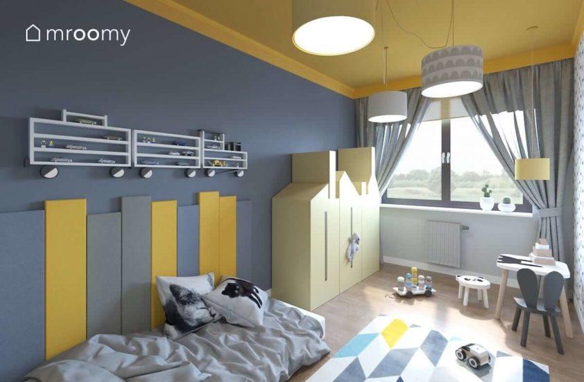 Żółta szafa w kształcie kamieniczki miękkie panele ścienne obok łóżka i kolorowy dywan w romby w pokoju dla małego chłopca