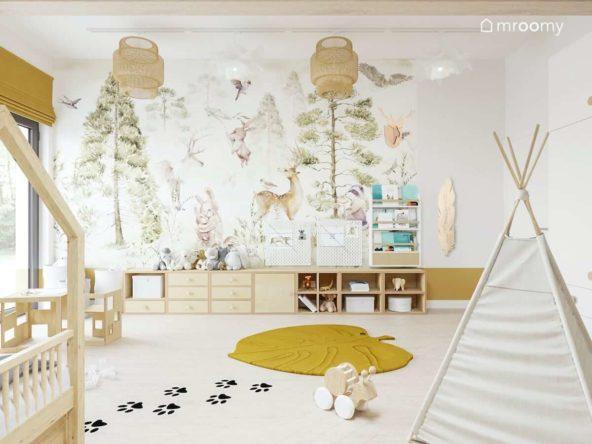 Leśna tapeta w pokoju małego chłopca z dywanem meblami ze sklejki i jasnymi tipi obok naklejki podłogowe