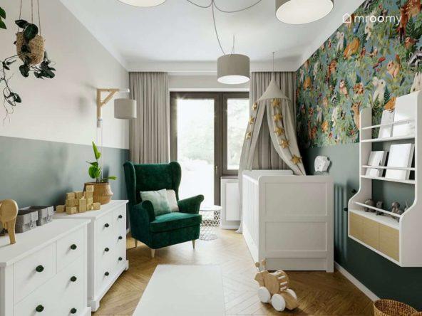 zielony fotel uszak białe łóżko dla niemowlaka i szary baldachim z gidlandą w niewielkiem pokoju dla dziecka