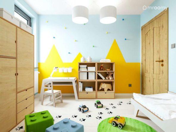Pokój małego chłopca z meblami ze sklejki i tapetą w żółte góry ze śladami łapek na podłodze