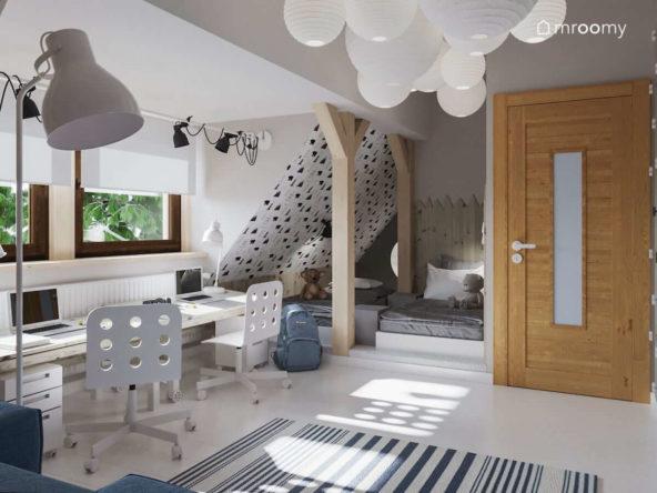 Pokój dla dwójki dzieci na poddaszu z dwoma biurkami pod oknem i miejscem do spania pod skosem